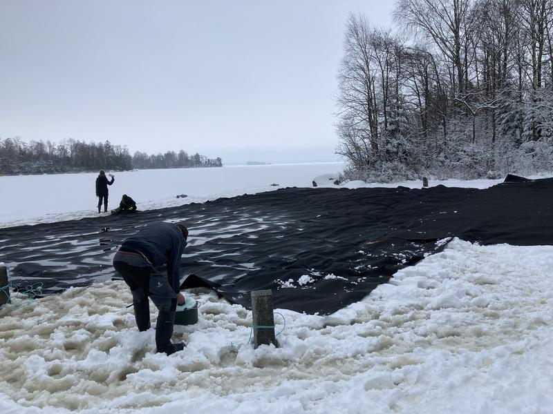 Täckduk läggs på isen på Bolmen